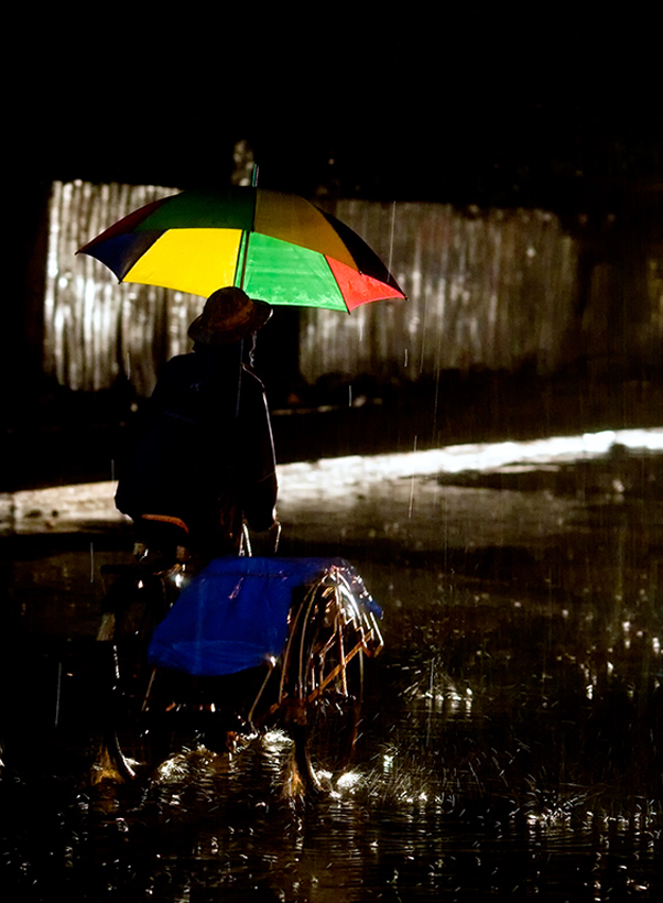 Bycycle trishaw driver in monsson rains Yangon Burma