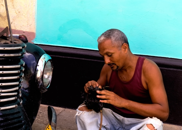 Maintaining Classic American vintage car on the streets in Trinidad
